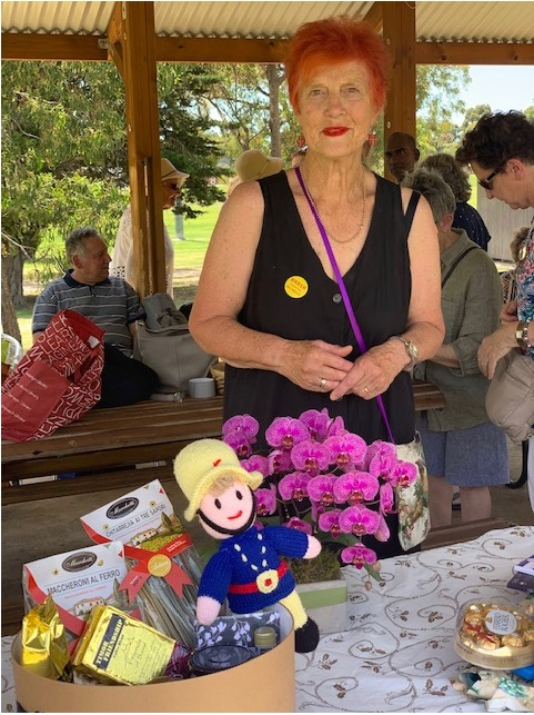 Catherine displaying raffle prizes from December 2020 picnic